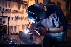 Employee welding aluminum using TIG. Welder in workshop stock image