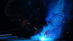 The welder works in a mask in slow motion. Sparks fly in different directions. Blue color glow welding. Work with steel