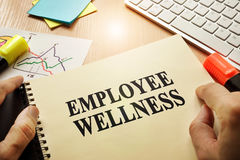 Employee Wellness. Hands holding documents with title Employee Wellness Stock Photography
