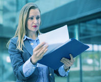 Employee woman with folder of documents. Employee woman in suit standing with folder of documents at the city royalty free stock photography