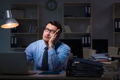 The employee working late at night at important report Royalty Free Stock Image