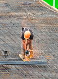 The employee works on the construction site. Performed   work electric tools for cutting reinforcement. Royalty Free Stock Photos