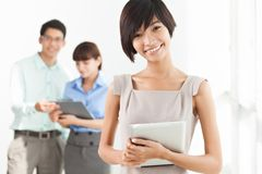 Employees. Image of business employees working in office, lovely girl being in the foreground royalty free stock image