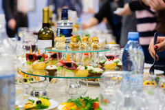 Employees of the company at the Banquet. Table with delicacies, alcohol and snacks. A gala reception Stock Images