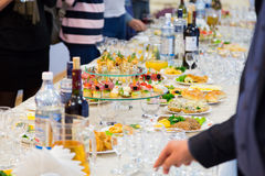 Employees of the company at the Banquet. Table with delicacies, alcohol and snacks. A gala reception Royalty Free Stock Photos