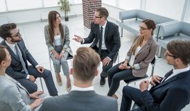 Employees of the company sitting in a circle and discussing work problems. Photo with text space royalty free stock image