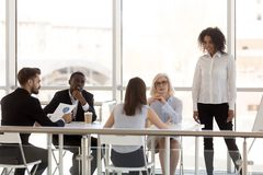 Employees discuss project at company business briefing. Diverse employees discuss startup project at business meeting in office, colleagues negotiate at table stock image