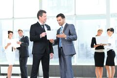 Employees discuss working papers, standing in the lobby Stock Photography