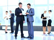 Employees discuss working papers, standing in the lobby. Of the office Royalty Free Stock Photo