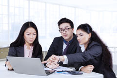 Employees discussing business plan in office. Three multi ethnic employees working in the office while discussing business plan with laptop on desk Stock Images