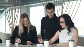 Employees are discussing at the desk on which the tablet lies. Two women and man are sitting at a white table, on which are closed cups. Nearby is a man in a stock footage