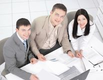 Employees discussing financial charts sitting at their Desk stock photos