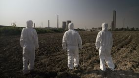 Team in hazmat suits looking at contaminated environment and agricultural area walking towards a nuclear power refinery -. Employees ecologists team in hazmat stock video