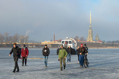 Employees of EMERCOM of Russia on the rescue ship Khivus-20 forbid people to go out on the melted ice on the frozen Neva river on Stock Photo