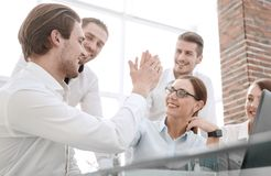 Employees give each other a high five sitting at the Desk. Success concept royalty free stock photography