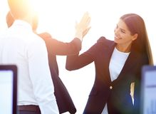 Employees giving each other high five. The concept of teamwork stock photos