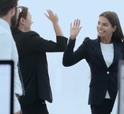 Employees giving each other high five. The concept of teamwork stock images