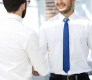 Employees greet each other by shaking hands. Standing in the office Royalty Free Stock Image