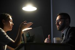 Employees having argument and business dispute in office at nigh. Two millennial businesspeople discussing work problems at night shift. Businessman and stock image