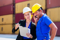 Employees in logistics company shipping containers. With clipboard Royalty Free Stock Images