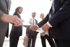 Employees look at the handshake business partners Stock Image