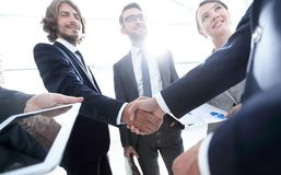 Employees look at the handshake business partners stock photos