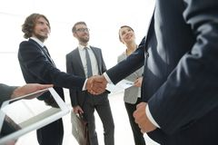 Employees look at the handshake business partners Royalty Free Stock Image