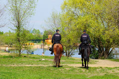 Employees Mounted Police patrol the relaxation area. Strogino. Moscow. Two police officers on horses patrol the embankment.People are resting near the water Royalty Free Stock Image