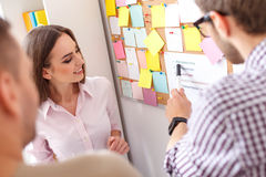 Employees near cork board with notes Stock Image