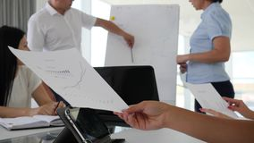 Employees near flipchart work with charts and offers ideas business development. In office stock footage
