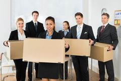 Employees in office holding cardboard boxes Royalty Free Stock Photo