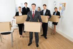 Employees in office holding cardboard boxes Stock Images