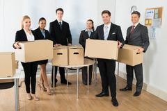 Employees In Office Holding Cardboard Boxes Royalty Free Stock Photography