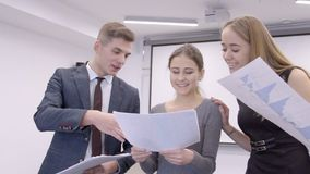 Employees of office study schedule of sales and pleased with result of leader. Three business people stand with papers on which are depicted charts and stock video footage