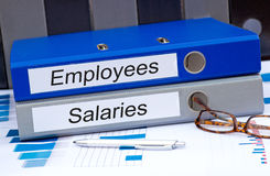 Employees and Salaries. Two binders on desk in the office Stock Photo
