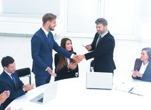 Business partners standing at a round table, shake hands after s Stock Photography