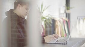 Small business employees in their office talking, laptop and smartphone. Employees of a small clothes shop, a man and two women, gathering to discuss work. Left stock footage