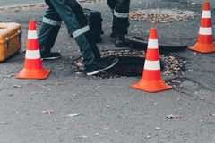 Employees of a telephone company near an open underground hatch. Repairing a communication line. Two guys in uniform with orange cones fencing troubleshoot royalty free stock photos
