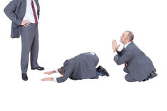 Businessmen begging their boss stock images