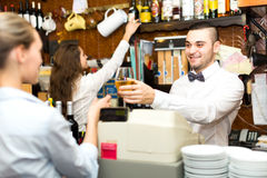 Employees working in a bar. Employees are working in a bar: handsome male bartender is giving a glass of white wine to a waitress while female barista is taking Stock Photography