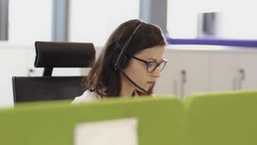 Employees working in call centre office with headsets stock video