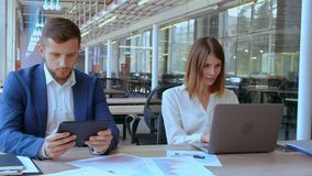 Employees works in open space office. Two young business workers focused sitting at the workplace in front of camera. woman typing on laptop near sits handsome stock video
