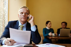Employer calling. Serious employer speaking on mobile phone with two managers on background Royalty Free Stock Photos