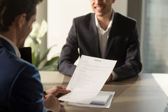 Employer conducting job interview, reviewing good resume of succ. Friendly employer conducting job interview, reviewing good resume of prepared skilled smiling Royalty Free Stock Images