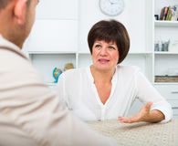 Employer discusses with elderly woman Stock Photo