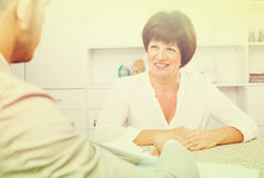 Employer discusses with elderly woman Stock Images