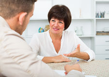 Employer discusses with elderly woman Stock Photography