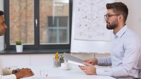 Employer having interview with employee at office. Job, business and employment concept - employer or hr manager having interview with indian male employee at stock footage