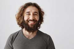 Employer is proud of his loyal employees. Portrait of glad attractive businessman with curly hair and beards smiling. Broadly seeing satisfied result and Royalty Free Stock Photo