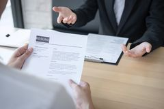 Employer or recruiter holding reading a resume during about colloquy his profile of candidate, employer in suit is conducting a royalty free stock photography